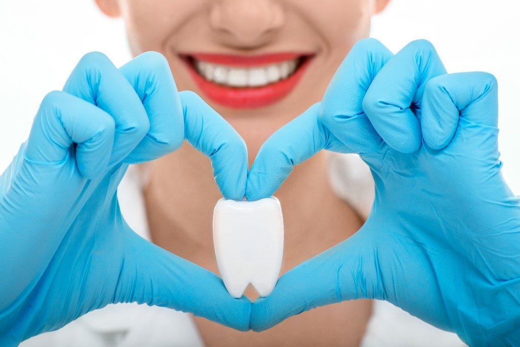 retrato de una joven dentista sujentando un diente con los dedos de su mano y formando un corazón